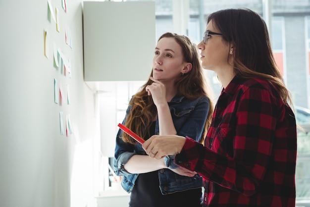 Dirigeants d'entreprise discutant sur des notes autocollantes