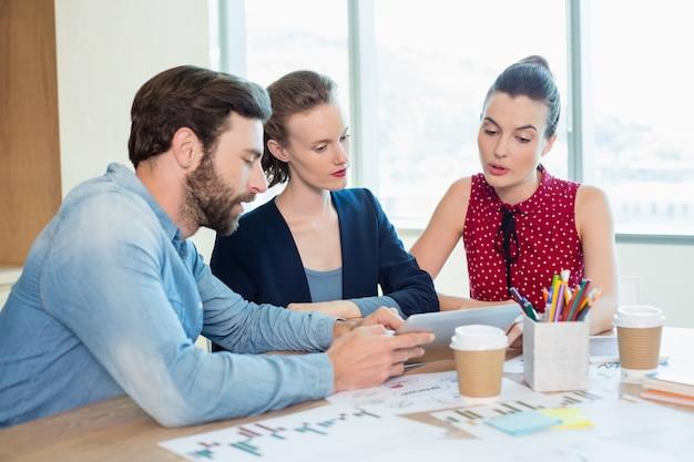 Les dirigeants d'entreprise discutant sur tablette numérique dans la salle de conférence