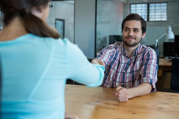 Dirigeants d'entreprise se serrant la main lors d'une réunion au bureau