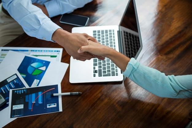 Dirigeants d'entreprise se serrant la main pendant la réunion