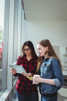 Dirigeants d'entreprises discutant sur tablette numérique tout en ayant une tasse de café