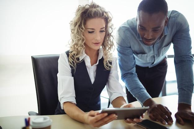 Dirigeants d'entreprises discutant sur tablette numérique