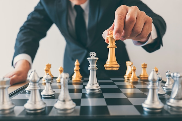 Les dirigeants d'hommes d'affaires jouant aux échecs et réfléchissant au plan stratégique sur le crash renversent l'équipe opposée et analysent le développement pour réussir en entreprise