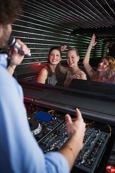Disc-jockey masculin jouant de la musique avec trois femmes dansant sur la piste de danse