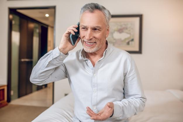 Discours d'affaires. homme d'affaires aux cheveux gris d'âge moyen parlant au téléphone et ayant l'air impliqué