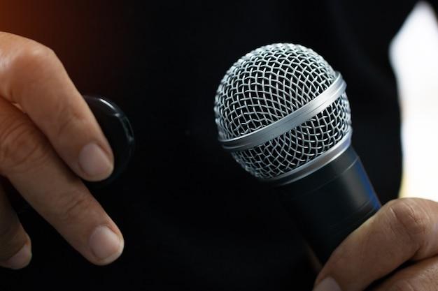 Discours d'homme d'affaires intelligent et parlant avec des microphones dans la conférence de séminaire