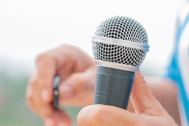 Discours d'homme d'affaires intelligent et parlant avec des microphones dans la salle de séminaire ou de conférence parlante