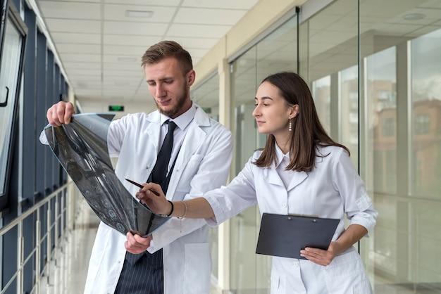 Discussion entre 2 médecins sur le traitement d'un patient regardant une irm cérébrale. santé