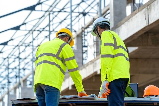 Discussion des ingénieurs avec l'architecte sur les détails du bâtiment sur le chantier de construction.
