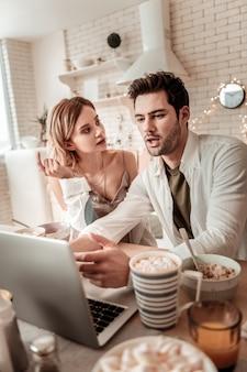 Discussion. jolie femme rayonnante aux cheveux longs portant des vêtements à la maison assis près de son mari