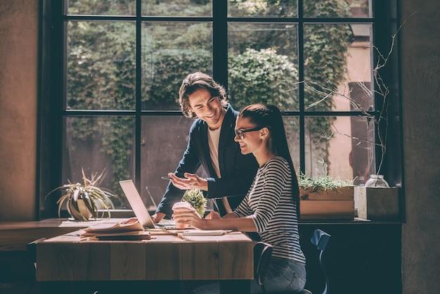 Discuter affaires ensemble. jeune homme et femme confiants regardant un ordinateur portable et souriant tout en étant assis au bureau en bois dans un bureau ou un café créatif