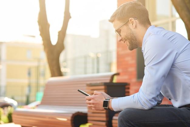 Discuter avec des amis jeune homme d'affaires heureux portant une chemise bleue et des lunettes à l'aide d'un smartphone