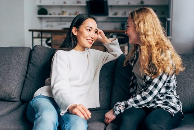 Discuter de joyeux meilleurs amis sur un canapé