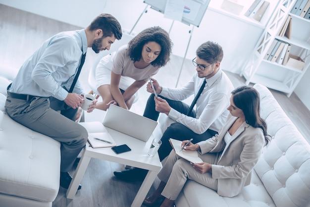 Discuter d'un nouveau projet. vue de dessus d'un groupe de quatre jeunes regardant un ordinateur portable assis sur le canapé au bureau