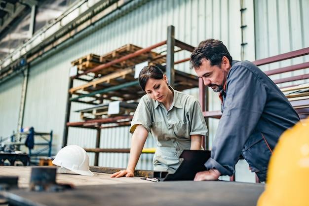 Discuter d'un projet dans une usine de l'industrie lourde.