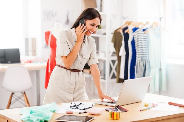 Discuter des tendances de la mode. belle jeune femme parlant au téléphone portable et travaillant sur un ordinateur portable en se tenant debout dans son atelier