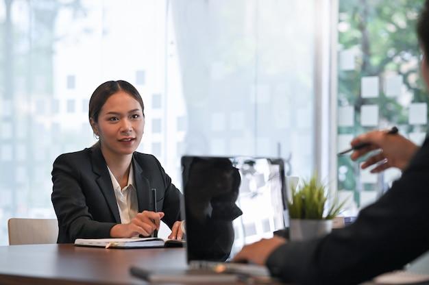 Discutez des affaires avec deux personnes consultant sur un ordinateur portable.