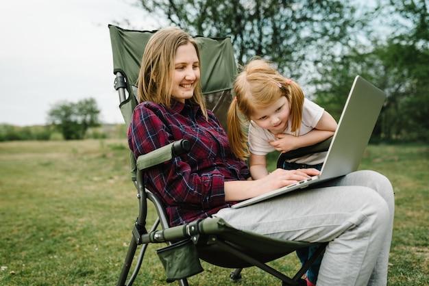 Discutez en ligne avec la famille sur un ordinateur portable lors d'un pique-nique dans la nature