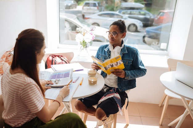 Discutons. jolie fille brune assise en position semi tout en se préparant à l'examen