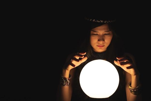 Diseuse de bonne aventure avec boule de cristal dans le noir. astrologie, concept de diseurs de bonne aventure.