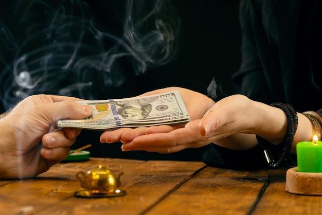 Une diseuse de bonne aventure ou un oracle prend de l'argent pour son travail. la bonne aventure à la main, la géromancie. lectures psychiques et concept de voyance