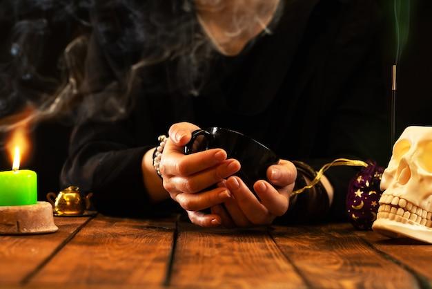 Diseuse de bonne aventure ou oracle avec une tasse noire à la main pour la bonne aventure sur le marc de café. lectures psychiques et concept de voyance