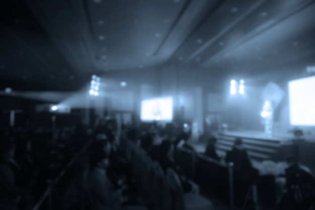 Disfocus des orateurs sur la scène sous la couleur pleine de downlight