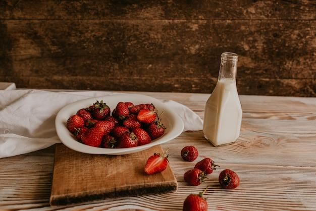 Dispersés de fraises rouges fraîches juteuses sur la table avec planche vintage. feuille de menthe. gouttes et éclaboussures de lait renversé.