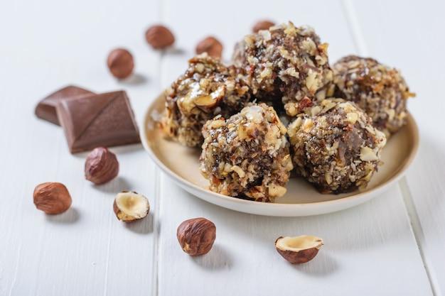 Dispersés sur un tableau blanc de noisettes et de bonbons de noix râpées et de fruits secs sur un tableau blanc. délicieux bonbons faits maison.