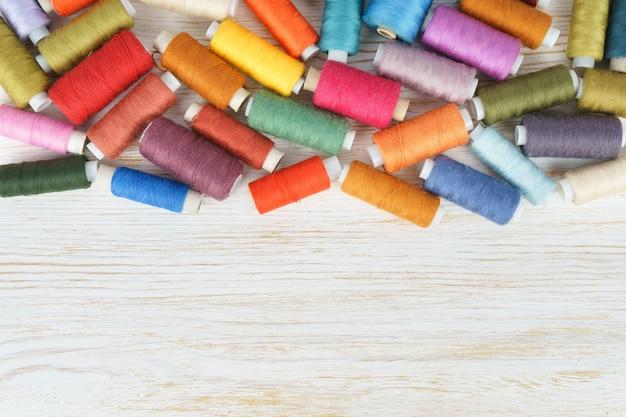 Dispersion de différentes couleurs de fils à coudre sur fond de bois blanc