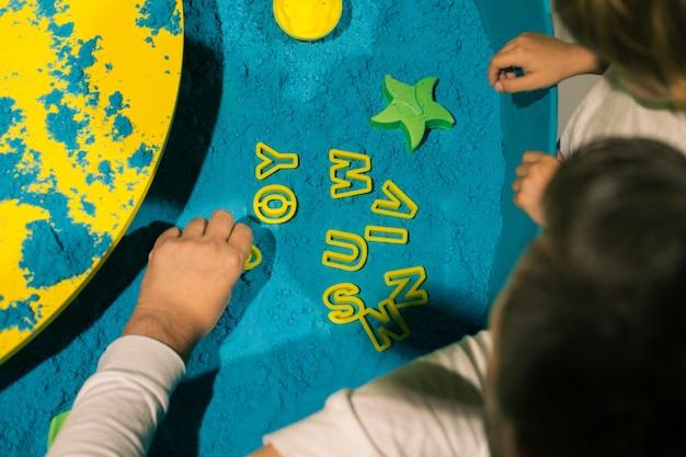 Disposer des mots à partir de sable cinétique. l'art-thérapie. soulager le stress et les tensions. sensations tactiles. créativité et plaisir. développement de la motricité fine. concentration et attention.