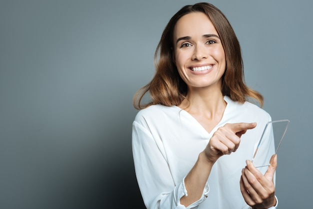 Dispositif innovant. joyeuse femme agréable positive tenant un smartphone et en l'utilisant tout en vous regardant