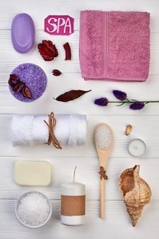 Disposition des accessoires de spa sur un bureau en bois blanc.