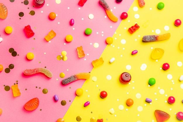 Disposition assortie de bonbons sur fond moitié rose et moitié jaune