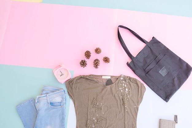 Disposition de base de vêtements pour femmes, extérieur sur fond pastel menthe pâle. concept de mode de vie. réveil. petit sac. sac