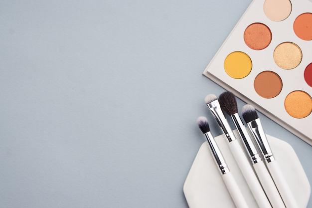 Disposition beauté sur un espace coloré avec des cosmétiques et des bijoux