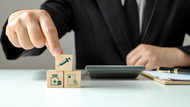 Disposition de blocs de bois empilés avec des icônes de soins de santé et des icônes médicales avec des mains humaines, le concept de choix des droits d'assurance maladie en cas de maladie