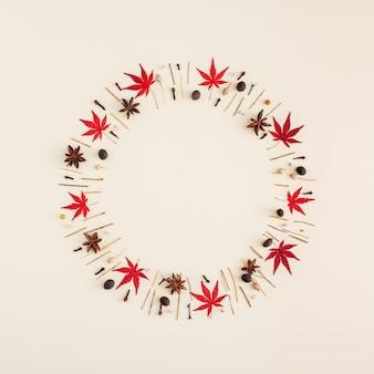 Disposition créative d'automne avec des feuilles et des branches disposées en cercle sur un fond de couleur crème. vision abstraite dans un style minimaliste. vue de dessus, mise à plat avec espace de copie.