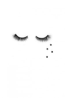 Disposition créative avec des cils. yeux fermés sur fond blanc