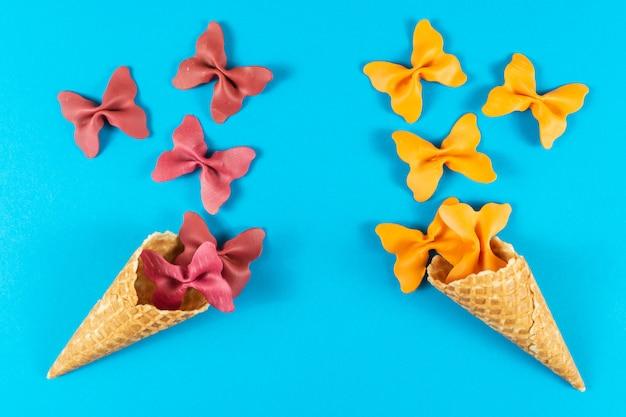Disposition créative estivale faite de cornet de crème glacée, de cornet de gaufre et de semoule de pâtes colorées