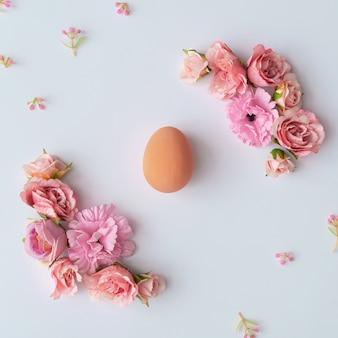 Disposition créative faite de fleurs printanières colorées et de feuilles vertes. concept de pâques minimal. modèle plat.