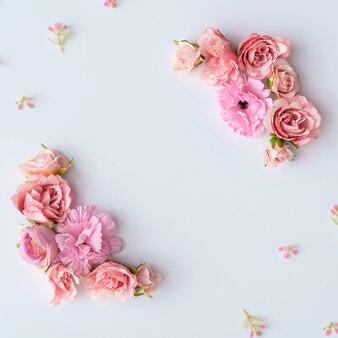 Disposition créative faite de fleurs printanières colorées et de feuilles vertes. concept de vacances minimal. modèle plat.