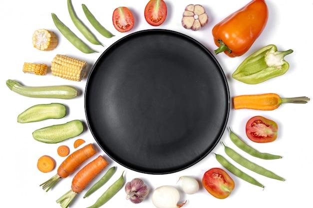 Disposition créative faite de haricots, tomates, poivrons, carottes, ail, maïs, courgettes, oignons et assiette noire.