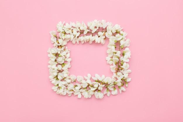 Disposition créative avec des fleurs blanches sur rose clair