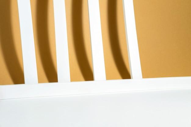 Disposition créative de lignes blanches géométriques avec des ombres dures sur un fond beige blanc dans les rayons du soleil. concept de fond minimal pour un produit, pour l'été ou l'automne