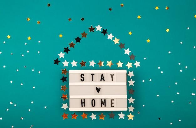 Disposition créative de noël avec lettrage de séjour à la maison et forme de maison en étoile. concept de pandémie de noël. disposition de la vue de dessus