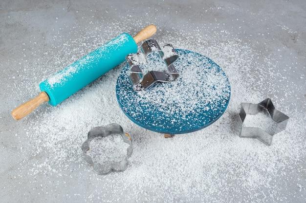 Disposition du rouleau à pâtisserie bleu, des moules à biscuits, du plateau et de la poudre de noix de coco sur une surface en marbre