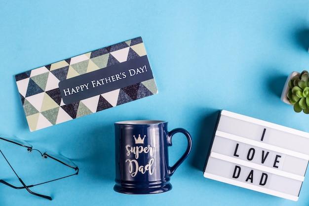 Disposition de la fête des pères avec un gobelet cadeau, une carte et l'inscription j'aime papa