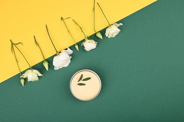 Disposition de fleurs et de crème naturelle. sur fond jaune-vert. bourgeons ouverts et fermés, place pour une inscription. mise à plat.