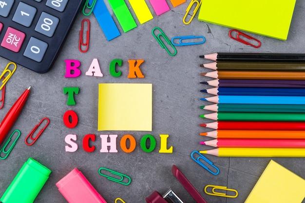 La disposition des fournitures scolaires sur un fond gris foncé.